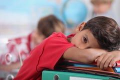 Muchacho soñoliento en sala de clase Imagenes de archivo