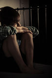 Muchacho solo que se sienta en su cama dentro de su sitio Fotografía de archivo libre de regalías