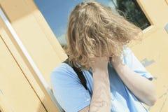 Muchacho solo triste en el patio de la escuela Foto de archivo