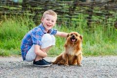 Muchacho sonriente agradable con un perro sonriente Mejores amigos outdoor Foto de archivo libre de regalías