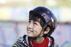Muchacho sonriente con el casco del monopatín Fotografía de archivo libre de regalías