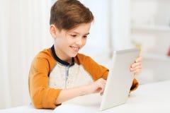 Muchacho sonriente con el ordenador de la PC de la tableta en casa Imagen de archivo libre de regalías