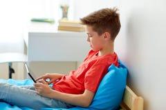 Muchacho sonriente con el ordenador de la PC de la tableta en casa Imagenes de archivo