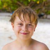 Muchacho sonriente con el pelo mojado en la playa Fotografía de archivo libre de regalías