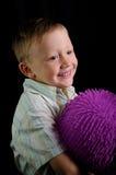 Muchacho sonriente con la bola de goma púrpura imagenes de archivo
