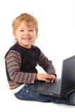 Muchacho sonriente con la computadora portátil Imagen de archivo libre de regalías