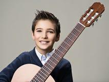 Muchacho sonriente con la guitarra Imagen de archivo