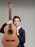 Muchacho sonriente con la guitarra Foto de archivo libre de regalías