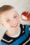 Muchacho sonriente con la manzana roja mordida Imagen de archivo libre de regalías