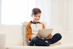 Muchacho sonriente con la tableta en casa Fotos de archivo