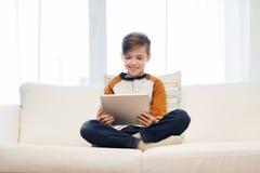 Muchacho sonriente con la tableta en casa Imágenes de archivo libres de regalías