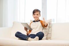 Muchacho sonriente con la tableta que muestra los pulgares para arriba en casa Fotos de archivo