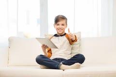 Muchacho sonriente con la tableta que muestra los pulgares para arriba en casa Imagen de archivo libre de regalías