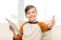 Muchacho sonriente con la tableta que muestra los pulgares para arriba en casa Fotografía de archivo