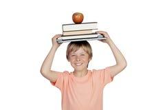 Muchacho sonriente con libros y una manzana oh su cabeza Imagen de archivo
