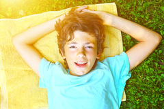Muchacho sonriente con los brazos bajo endecha principal Imagen de archivo