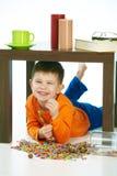Muchacho sonriente con los dulces debajo de la tabla en casa interior imágenes de archivo libres de regalías