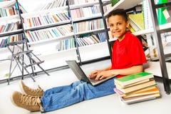 Muchacho sonriente con los libros y el ordenador portátil en biblioteca Imágenes de archivo libres de regalías