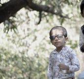 Muchacho sonriente con los vidrios de sol en parque imagenes de archivo
