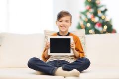 Muchacho sonriente con PC de la tableta en casa en la Navidad Foto de archivo