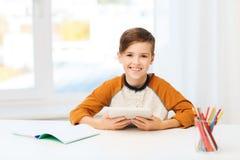 Muchacho sonriente con PC y el cuaderno de la tableta en casa Foto de archivo