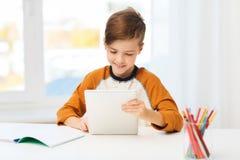 Muchacho sonriente con PC y el cuaderno de la tableta en casa Imagen de archivo libre de regalías