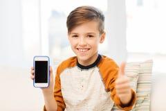 Muchacho sonriente con smartphone en casa Imágenes de archivo libres de regalías