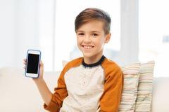 Muchacho sonriente con smartphone en casa Imagen de archivo libre de regalías