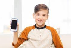 Muchacho sonriente con smartphone en casa Foto de archivo