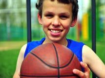 Muchacho sonriente con un baloncesto en la corte Fotografía de archivo