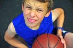 Muchacho sonriente con un baloncesto que se sienta en corte Imagen de archivo libre de regalías