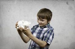 Muchacho sonriente con un piggybank Foto de archivo libre de regalías