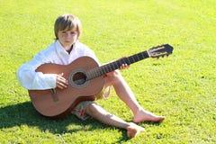 Muchacho sonriente con una guitarra Fotos de archivo libres de regalías