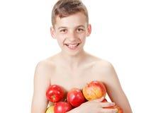 Muchacho sonriente con una pila de manzanas foto de archivo libre de regalías