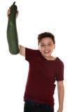 Muchacho sonriente de consumición sano del adolescente con el calabacín Imagen de archivo libre de regalías
