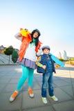 Muchacho sonriente de la anchura de la mujer que lleva a cabo color plástico Imagenes de archivo