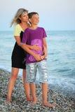 Muchacho sonriente de los abrazos de la mujer joven en la playa Imagen de archivo libre de regalías