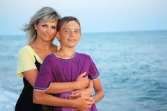 Muchacho sonriente de los abrazos de la mujer joven en la playa Imágenes de archivo libres de regalías