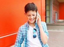 Muchacho sonriente del adolescente del retrato que habla en el teléfono Imágenes de archivo libres de regalías