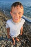 Muchacho sonriente del adolescente que se coloca en la costa Foto de archivo libre de regalías