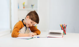 Muchacho sonriente del estudiante que escribe al cuaderno en casa Fotografía de archivo libre de regalías
