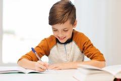 Muchacho sonriente del estudiante que escribe al cuaderno en casa Imagenes de archivo