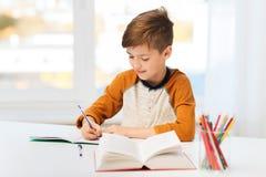 Muchacho sonriente del estudiante que escribe al cuaderno en casa Imágenes de archivo libres de regalías