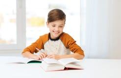Muchacho sonriente del estudiante que escribe al cuaderno en casa Fotos de archivo libres de regalías