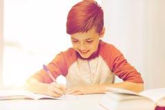 Muchacho sonriente del estudiante que escribe al cuaderno en casa Foto de archivo