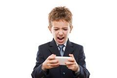 Muchacho sonriente del niño en el traje de negocios que juega a juegos o que practica surf Internet en el ordenador del smartphon Imagen de archivo