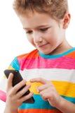 Muchacho sonriente del niño que habla el teléfono móvil o el smartphone Foto de archivo