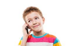 Muchacho sonriente del niño que habla el teléfono móvil o el smartphone Imágenes de archivo libres de regalías