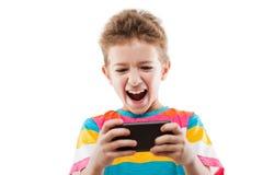 Muchacho sonriente del niño que juega a juegos o que practica surf Internet en smartphon Foto de archivo libre de regalías