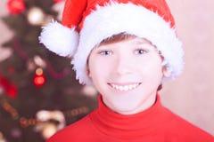 Muchacho sonriente del niño que lleva el sombrero de santa sobre luces de la Navidad Fotografía de archivo